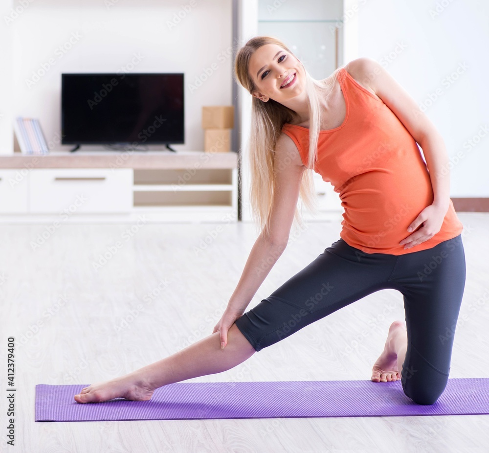 Fototapeta Pregnant woman doing sport exercise at home