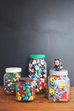 A Collection Of Vintage Toys Arranged In Jars On A Desktop