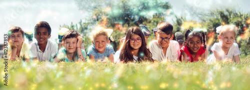 Fotografia Happy team of friends children resting on grass together in park