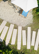 Aerial View Of Relaxing Area With White Beach Umbrella And Lounge Chair Near Pathway On Tropical Climate.