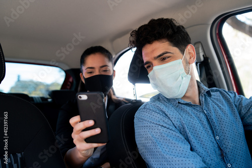 Woman showing something on phone to cab driver. Fototapet