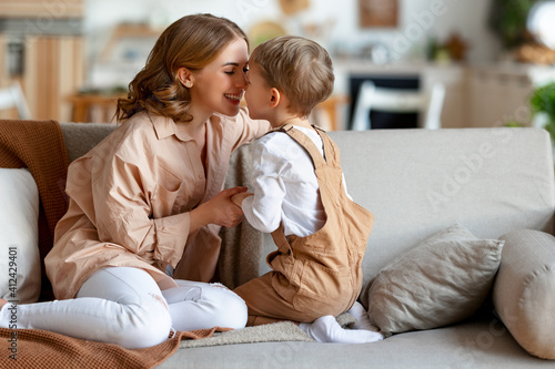 Happy mother hugging son on sofa #412429401