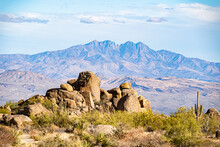 The Boulders In The Desert And The Mountains In The Distance Define This Landscape