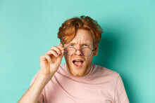 Close Up Portrait Of Redhead Guy Take-off Glasses And Looking Confused At Something Strange, Standing Shocked Over Turquoise Background