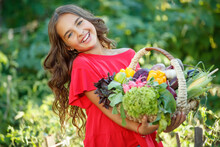 Little Girl In The Vegetable Garden. Child With Vegetables. High Quality Photo.