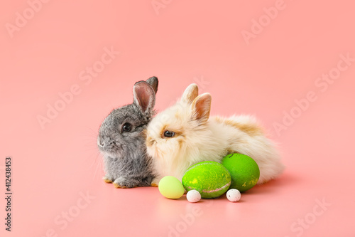 Photo Cute rabbits and Easter eggs on color background