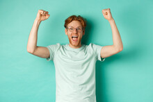 Young Redhead Man Feeling Like Champion, Raising Hands Up In Fist Pump Gesture And Shouting Yes With Joy, Winning Prize, Triumphing Of Success, Standing Over Mint Background