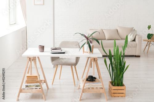 Fototapeta Modern work place in living room or studio, natural light, home plants obraz