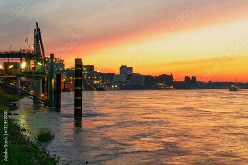 Fotografia, Obraz Sea By Illuminated Buildings Against Sky During Sunset