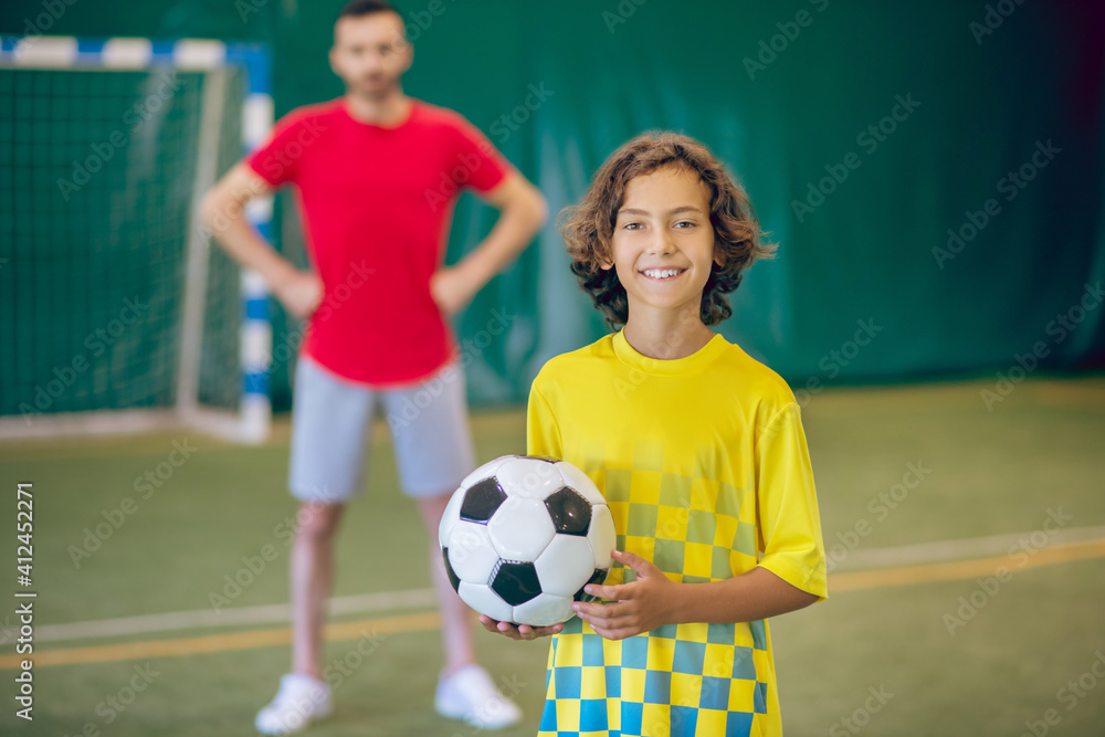 Fototapeta Cute boy in yellow uniform feeling good at PE lesson