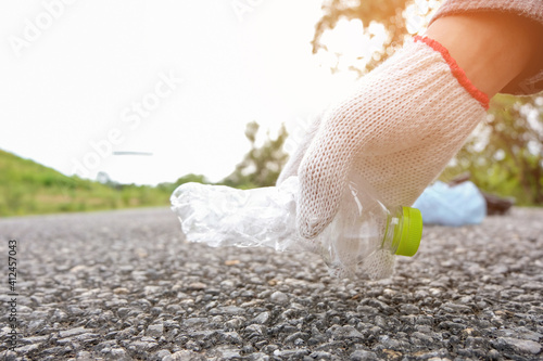 Cropped Image Of Hand Picking Plastic Bottle On Footpath Fototapet