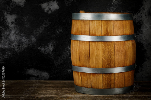 Papel de parede A beautiful wooden barrel and a worn oak wood table set against a dark wall patt