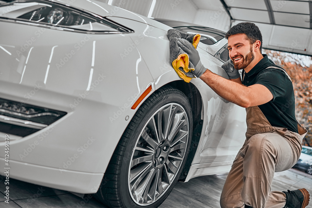 Fototapeta Man cleaning car and drying vehicle with microfiber cloth. Hand wipe down paint surface of shiny white car after polishing and ceramic coating.