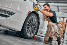 Car Detailing Series. Worker Cleaning White Car.