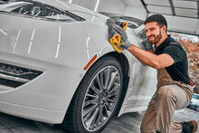 Man Cleaning Car And Drying Vehicle With Microfiber Cloth. Hand Wipe Down Paint Surface Of Shiny White Car After Polishing And Ceramic Coating.