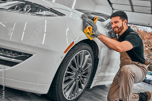 Fototapeta Man cleaning car and drying vehicle with microfiber cloth. Hand wipe down paint surface of shiny white car after polishing and ceramic coating. obraz