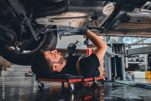 Male car mechanic worker working using wrench tool for repair, maintenance underneath car Fototapet