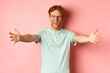 Leinwandbild Motiv Young friendly man with red hair and beard reaching hands for hug, stretch out arm in warm welcome, smiling happily, standing over pink background