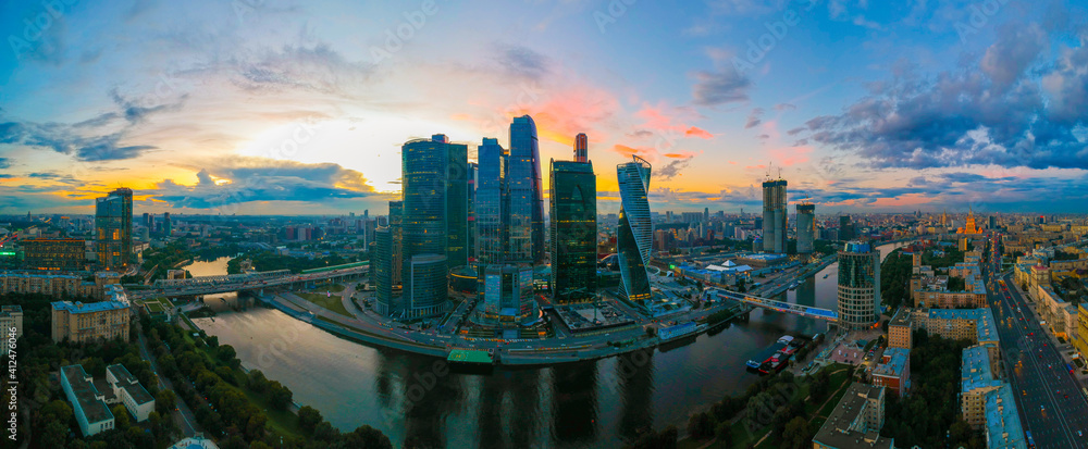 Fototapeta Large panorama view of summer Moscow with skyscrapers of Moscow-City - a business district on the embankment of Moskva River at sunset, Russia. Top view aerial cityscape from the drone.