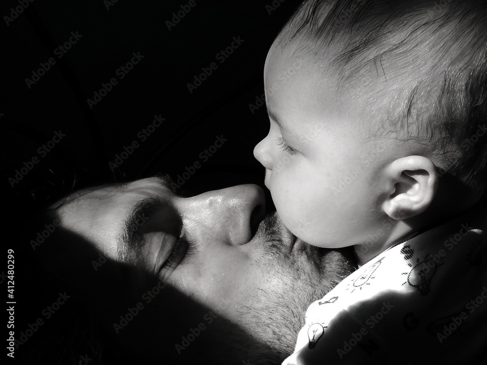 Fototapeta Close-up Of Father Kissing Son Against Black Background