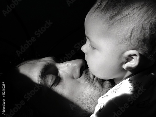 Fototapeta Close-up Of Father Kissing Son Against Black Background obraz