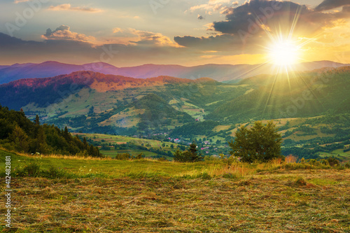 Fototapeta mountainous rural landscape at sunset. grassy meadow on top of a hill. clouds above the ridge in evening light. view in to the distant valley obraz