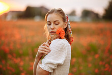 Girl In A White Dress With A Poppy Flower In Her Hands