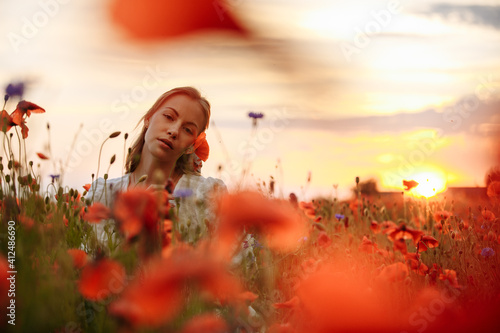 Fotografia girl in a white dress in a field of poppies on a sunset background
