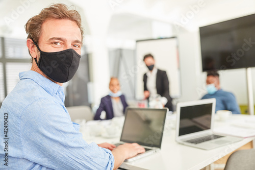 Business man with face mask on laptop - fototapety na wymiar