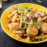 Caserecce pasta with meatballs in  sweet and sour sauce and vegetables in bowl.