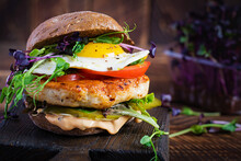 Hamburger. Sandwich With Chicken Burger, Tomatoes,  Pickled Cucumber And Fried Egg. Fresh Tasty Chicken Burger On Wooden Table.