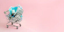 Concept Of Vaccination Against Viruses.Medicines, Syringes, Pills And Masks In A Small Shopping Cart On Pink Background.