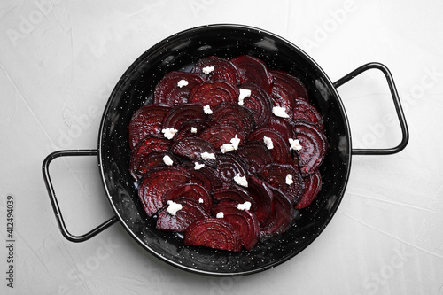 Roasted beetroot slices with feta cheese in wok pan on light grey table, top view