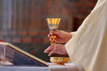 Chalice In The Hands Of The Priest On The Altar During The Celebration Of The Mass