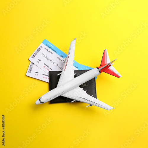 Leinwand Poster Toy airplane and passport with tickets on yellow background, flat lay