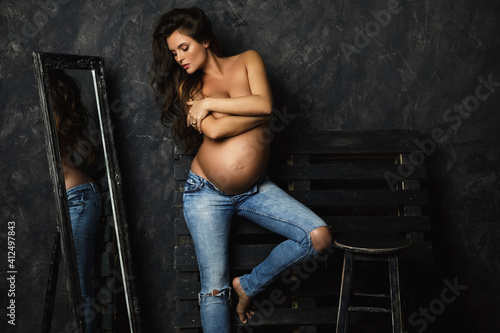 Portrait of young pregnant woman wearing jeans with beautiful long hair