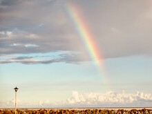 Low Angle View Of Rainbow Over Landscape Against Sky