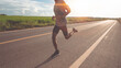 Low Section Of Man Running On Road Against Sky