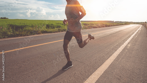 Obraz Low Section Of Man Running On Road Against Sky - fototapety do salonu