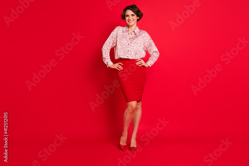 Obraz Full length body size view of attractive cheerful brown-haired girl posing hands on hips isolated over bright red color background - fototapety do salonu