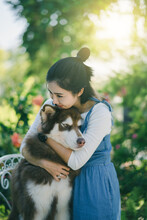 Smiling Woman Embracing Siberian Husky Against Plants