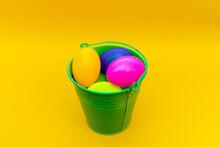 Easter Plastic Eggs In A Metal Green Bucket Indoors Studio Shot.