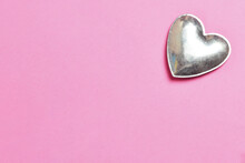 Metal Heart On Pink Paper Background
