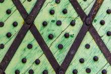 Green Wooden Background With Metal Rivets. Detail Of Old Wooden Gates, Doors With Cracked Paint. Black And White Old Wooden Planks