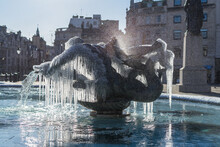 Frozen Fountain Statues Of Trafalgar Square In London. Icicles Mystically Hanging Off Bronze Water Fountain