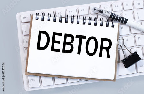 debtor. text on white paper on white keyboard Fototapet