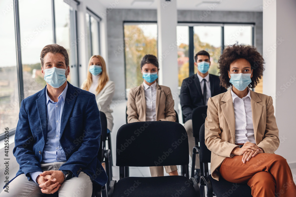 Fototapeta Group of multicultural business people with face masks sitting and listening presentation in corporate firm during corona virus.
