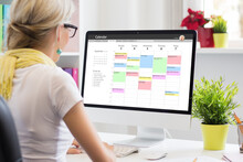 Woman Using Calendar App On Computer In Office