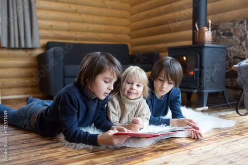 Fototapeta Three sweet children, siblings lying on the floor in little fancy wooden cottage