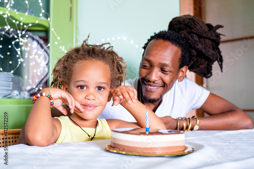 Tela portrait of happy mixed race son and african father, celebration with chocolate